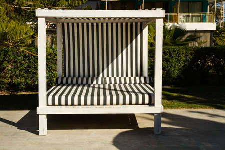 A striped black and white balinese bed in the garden