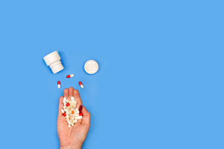 Woman hand holding medical pills on a blue background Standard-Bild