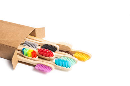 Colored bamboo wood thoothbrush in a cardboard box on a white background