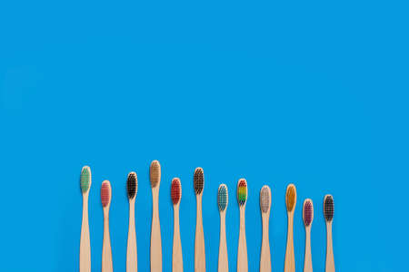 Colored bamboo wood toothbrushes on a blue background