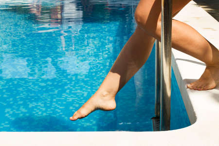 Woman with her foot close to the water in a swimming pool
