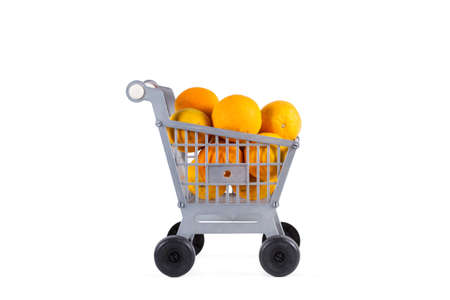 A plastic toy shopping cart with oranges on a white background Standard-Bild