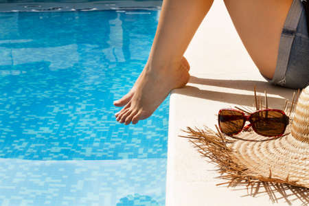 Woman sitting in the edge of a swimming pool in sunny day