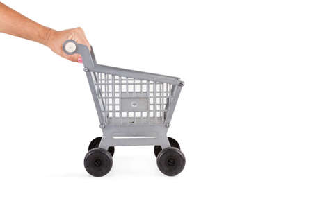 Woman hand pushing a plastic toy shopping cart on a white background Standard-Bild