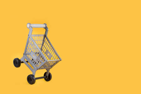 A plastic toy shopping cart on a yellow background Standard-Bild