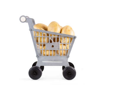 A plastic toy shopping cart with potatoes on a white background