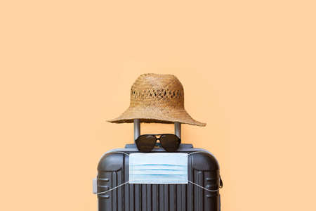 A suitcase with a hat, sunglasses and surgical mask