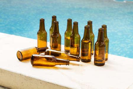 Empty beer bottles in the edge of a swimming pool Standard-Bild