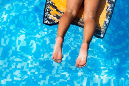 Girl legs on an infant float in a swimming pool Standard-Bild