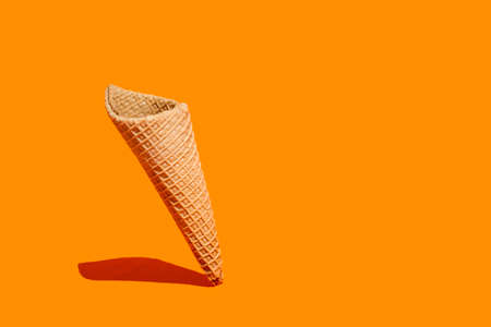 Sweet wafer cone on an orange background with copy space