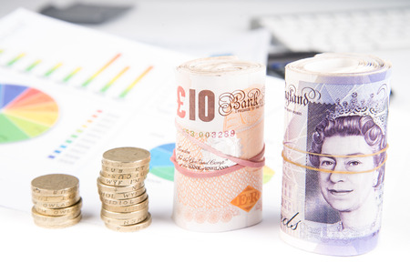 fluctuate: British pound sterling coins and notes with financial chart in background