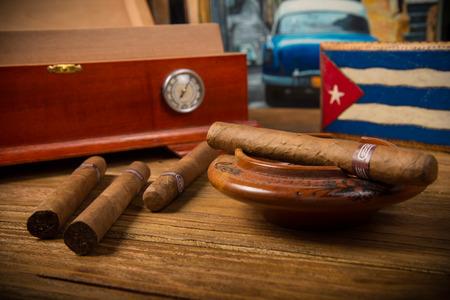cigarro: Los cigarros cubanos y humidor con cenicero en la mesa de madera rústica con la pintura cubana del viejo coche americano en el fondo