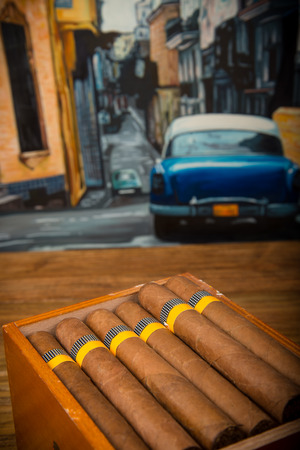 pleasure craft: Cuban cigars and humidor on rustic wooden table with Cuban painting of american old car in background Stock Photo