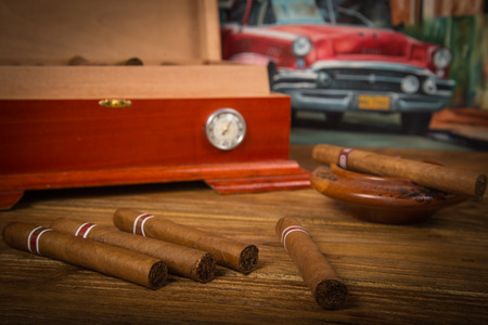 Cuban cigars and humidor with ashtray on rustic wooden table with Cuban painting of american old car in background photo