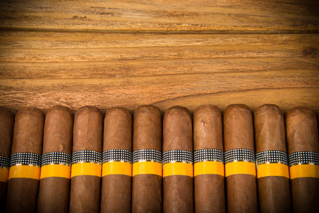 Cuban cigars on rustic wooden table in line on the edge of background photo