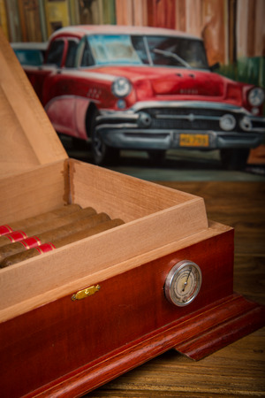 Cuban cigars and humidor on rustic wooden table with Cuban painting of american old car in background photo
