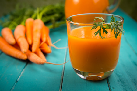 carrot juice: Homemade natural carrot juice in glass on rustic blue wooden table in background