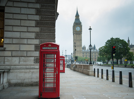 Red classic phone booth box with London landmark Big Ben in background