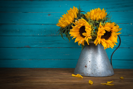Fresh sunflower flowers in rustic antique vase on wooden table and rustic background