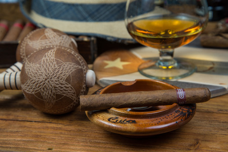 Cuban cigars and Rum or other alcohol in glass on table top view with vintage wooden background photo