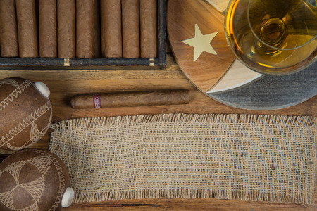 Cuban cigars and Rum or other alcohol in glass on table top view with vintage wooden background and copy space photo
