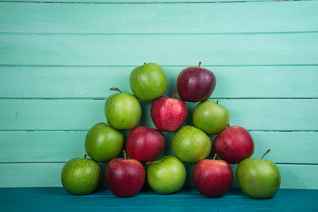 Farm fresh pyramid of organic red and green autumn apples on wooden retro pastel color table and wood background photo
