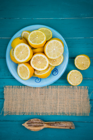 juice squeezer: Market fresh organic lemons halves on wooden table background with copy space and juice squeezer