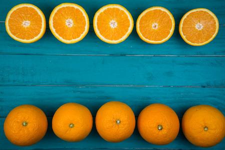 Verse organische sinaasappelenvruchten op blauwe houten achtergrond met exemplaarruimte