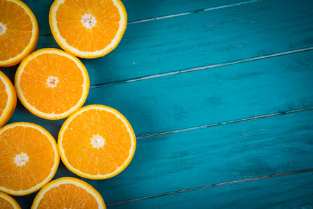 Fresh organic oranges halves  fruits on blue wooden background with copy space Foto de archivo
