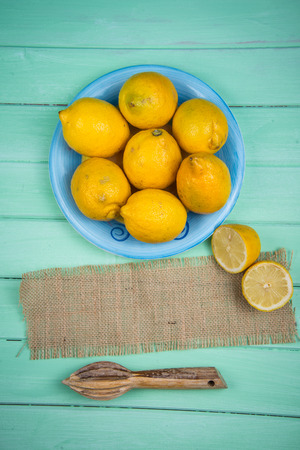 juice squeezer: Market fresh organic lemons and juice squeezer on wooden table background with copy space
