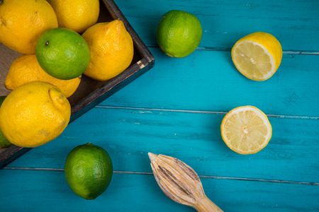 juice squeezer: Market fresh organic lemons and limes and juice squeezer on wooden table background