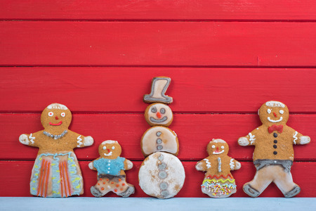 Happy funny gingerbread man family on wooden background with Snowman photo