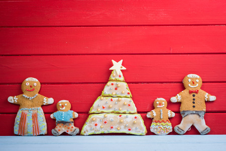 Glückliche lustige Lebkuchenmann-Familie auf Holzuntergrund mit Weihnachtsbaum Standard-Bild - 32328174