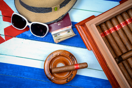 cuban culture: Cuban cigars with straw hat and humidor on flag background Stock Photo