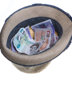 straw hat filled up with cash isolated on white photo
