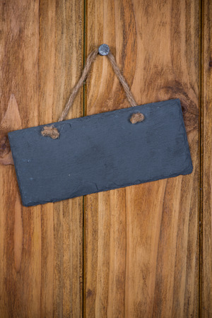 Stone signboard with rope hanging on wooden background photo