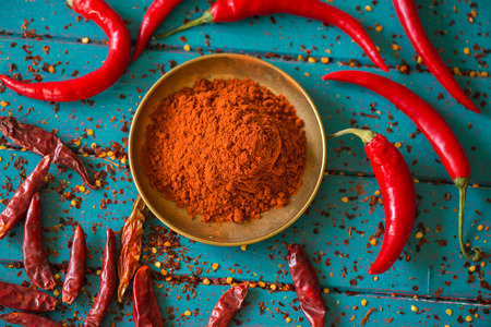Chilli powder and fresh and dried peppers on table background