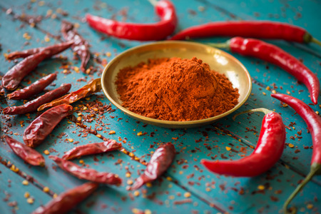 chili powder: Chilli powder and fresh and dried peppers on table background