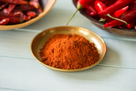 chilli powder in bowl with dried and fresh peppers in background on white wood table