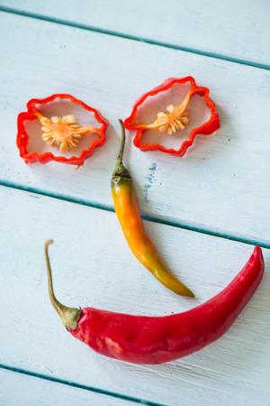Lächeln lustiges Gesicht mit Hot Chilli Peppers auf Holztisch gemacht