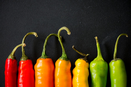 many vibrant colors on peppers on black slate bacground