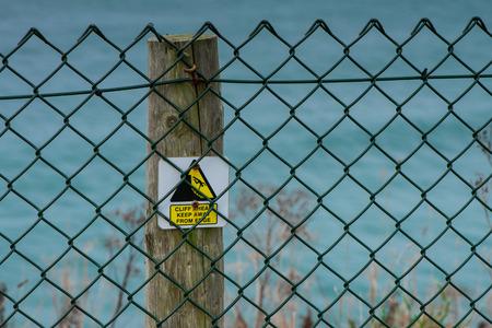steep cliff sign: Cliff hazard sign on wooden post Stock Photo