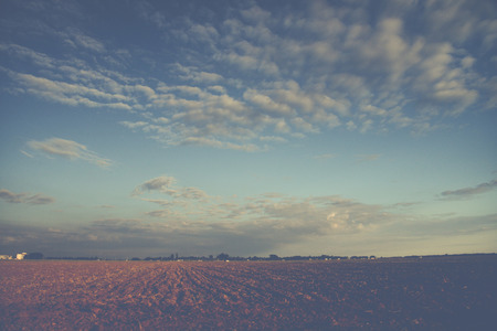 cross processed: blue sky and cluds over farm land in vintage style