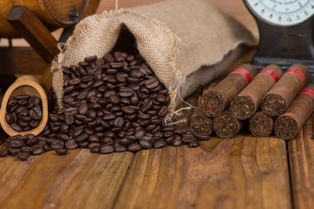 Cuban cigars and rust coffee beans on wood photo
