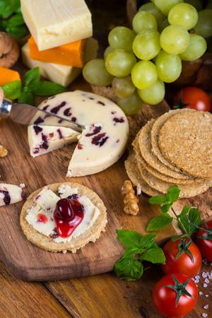 tabla de queso: Abridores saludables en r�stica tabla de quesos de madera Foto de archivo