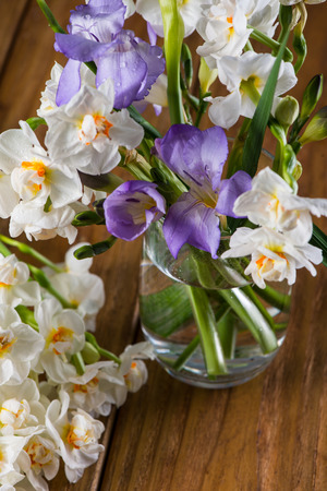 fresh garden flowers in glass on wooden table photo