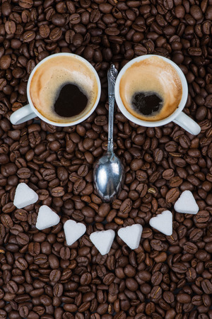 Smiling face made from cup of frersh coffee ,sugar and silver spoon photo