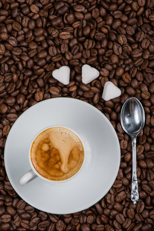 expresso: overhead view on cup of expresso coffee  and roasted beans with sugar and silver spoon