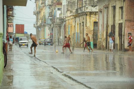 HAVANA, CUBA - MAY 31, 2013 Locan Cuban kids play football or soccer on street in Havana, Cuba while tropical storm aproching with heavy rain but very hot air.