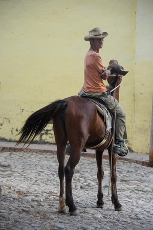 communists: TRINIDAD, CUBA - JANUARY 28, 2013 Cuban local man sitting on horse  and posing to photos  on street in UNESCO protected city of Trinidad, Cuba.